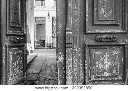 Black And White Photo Of Shabby Double Door Surface With Peeling Paint. Opened Door To Patio Inside