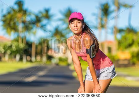 Tired runner woman ready for running wearing sports cap and sport armband with earphones listening to mobile music. Active fit Asian girl resting taking a jogging break on outdoor summer street. poster