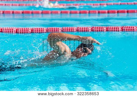 Swimmer man fitness training at swimming pool. Professional male athlete doing crawl freestyle stroke technique.