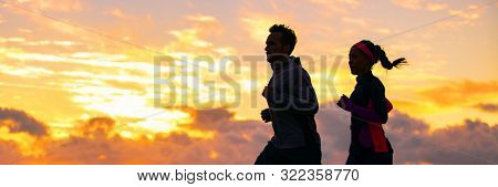 Run fit couple sport banner panorama of runners friends woman and man training cardio together running on outdoor race at sunset panoramic background. Silhouettes of two athletes working out.