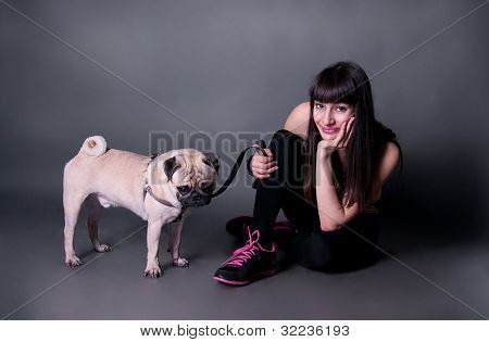 Sport Girl With A Pug Dog In Studio