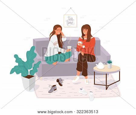 Two Young Women Spending Time Together. Girls Cosy Sitting On The Couch, Talking And Holding Cup Tea