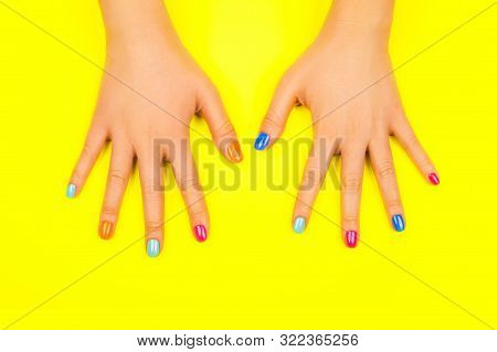 Beautiful Female Hands With Manicure In Trendy Neon Colors On Bright Yellow Background. Beauty Conce
