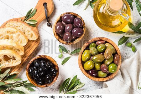 Olives In Wooden Bowls, Ciabatta And Olive Oil On White Background. Top View With Copy Space.