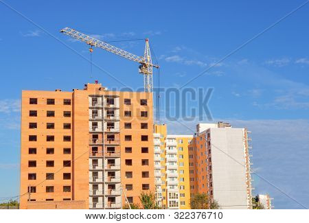 Brick multistory building under construction with crane on the site, new condominium on the background poster