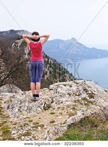 Girl  standing on precipice above sea