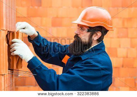 Construction Worker Contractor Man. Orange Buid Background. Bricklayer Industrial Worker Installing