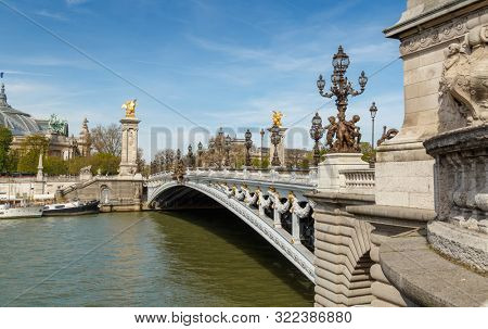 Paris, France, March 31, 2017: Pont Alexandre III in Paris, spanning the river Seine. Decorated with ornate Art Nouveau lamps and sculptures. The most ornate, extravagant bridge in Paris