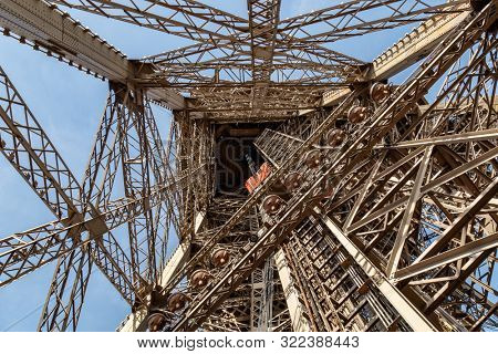 Paris, France, March 30, 2017: Inside the Eiffel Tower in Paris, France. View to the inside of Eiffel Tower. Big symetrical building. Close up shot in the morning. Blue sky with a sunny weather