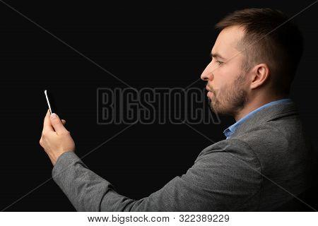 Caucasian Businessman Using Facial Recognition As Security Software On Cellphone, Black Studio Backg