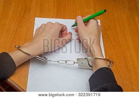 Female Hands With Handcuffs Fill Out A Police Record, Confession. Arrest, Bail, Crime, Prison.