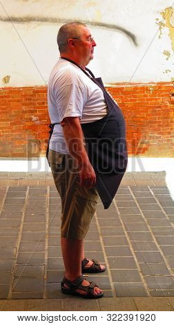 Alora, Spain - August 12, 2019: Local Bar Owner Waiting For Customers Outside His Cured Ham Shop And