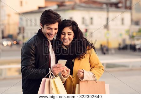 Consumerism Concept. Happy Couple Using Cellphone After Shopping In City Mall, Free Space