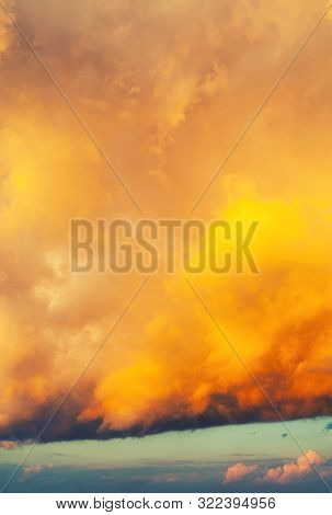 Orange bright dramatic sky background - picturesque colorful clouds lit by sunlight. Vast sky landscape panoramic scene, colorful sky view, golden colorful sky scene