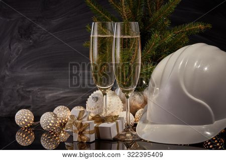 Construction hard hat, wineglasses with champagne, gift boxes and Christmas ornament on black background. Construction New Year, Christmas background with copy space. For greeting card or advertising