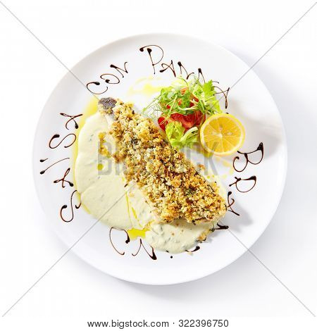 Exquisite serving white restaurent plate of breaded pike perch or zander fillet with cream sauce isolated topview. Restaurant main course with fried sander fish or pike meat with lemon and greens poster