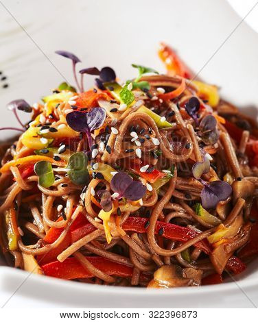 Macro shot of japanese soba, yakisoba or nagano soba with vegetables in sweet and sour sauce. Thin buckwheat noodles, pasta or tagliatelle with greens and sesame on white restaurant plate isolated