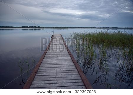 Wooden Pier On A Grassy Lake Near The Shore, Overcast In The Morning