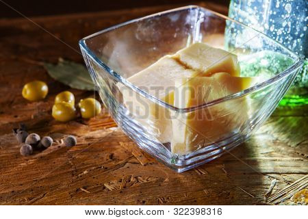 Slices of parmesan cheese and spices on the kitchen table