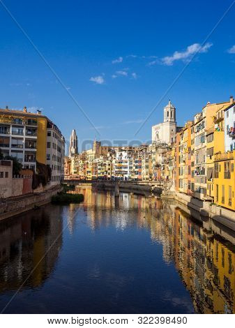 Girona's Tipical Skyline Cityscape Over The Onyar River With Colourful River Houses On A Blue Sunny