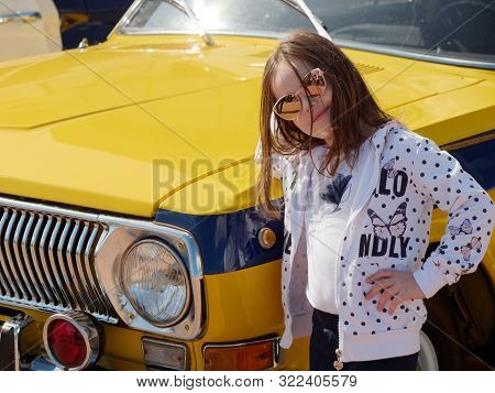 Beautiful Girl In Glasses On A Yellow Car