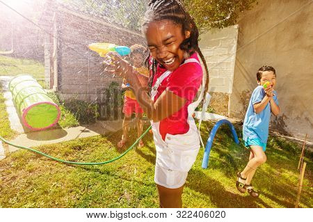 Girl With Group Of Kids Play Water Pistol Fight