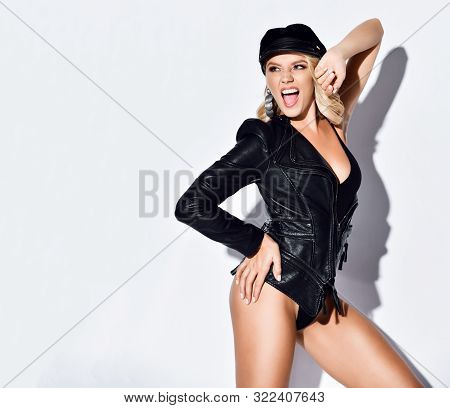 Portrait Of Playful Blonde Woman In Black Bodysuit, Modern Stylish Leather Jacket And Cap Posing Scr