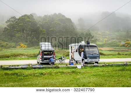 Motorhome Rv And Campervan Are Parked On A Beach. Surfers On Vacation Are Packing Surfboards Or Boar