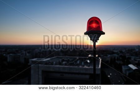 A red glass lantern of obstruction lights, mounted on the roof of a skyscraper to ensure flights safety, is located against the backdrop of the sun setting over the city and the roofs of other buildings. poster