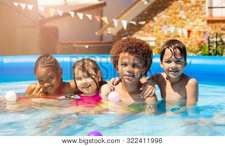 Four Kids Play In Backyard Swimming Pool Together