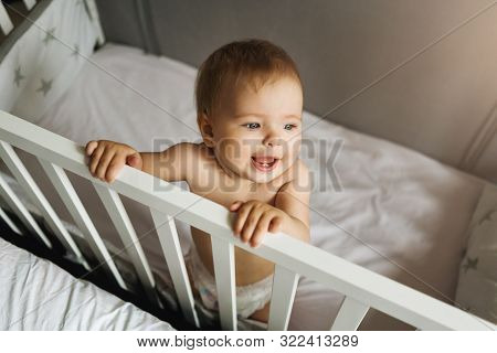Top View. A Child Alone Stands At Home In A Crib Holding On To Her Side. Portrait Of A Nine-month-ol