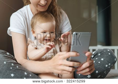 Nine-month-old Baby Girl Sits With Her Mother On Bed And Looks On Smartphone Cartoons, Plays Game. C