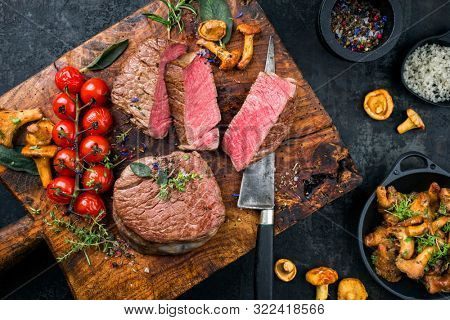 Fried dry aged beef fillet medallion steak natural with tomatoes and herbs as top view on a wooden cutting board