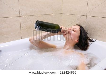 Funny Young Adult Woman Drinking Wine From Bottle Lying Relaxing In Bath Tub With Foam. Smiling Tips