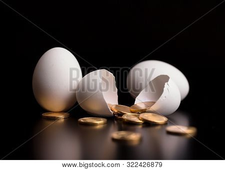 Gold Coins In An Open Egg. The Concept Of Financial Assets. Chicken Eggs And Gold Coins On A Black B