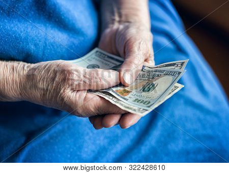 Dollar Bills In The Hands Of An Elderly Man. A Pensioner Holds Money In His Hands. Elderly Man Holdi