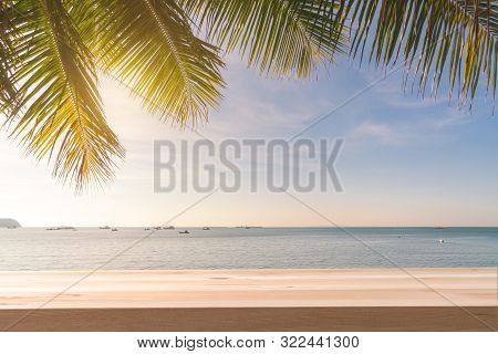 Wooden Table With Coconut Plam Tree And Sunset At Tropical Beach, Summer Vacation Concept