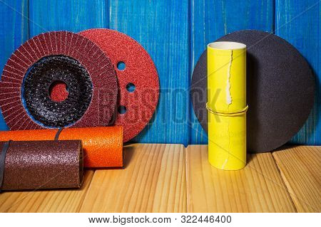 Set of abrasive tools and sandpaper blue wood background the wizard is used for grinding items poster