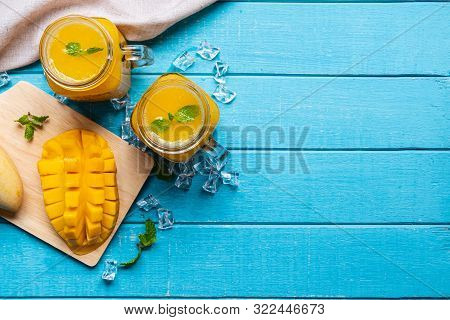 Refreshing Mango Smoothies In Glass With Ripe Mango On Wooden Table And Copy Space, Top View