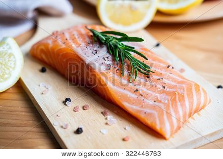 Fresh Salmon Steak With Herbs, Lemon And Ingredients For Cooking In Kitchen