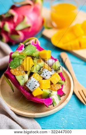Mix Tropical Fruits Salad Served In Half A Dragon Fruit On Wooden Table