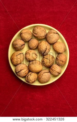 Walnuts In A Plate On A Red Background.