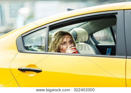 Photo Of Young Woman Drinking Coffee While Sitting In Back Seat Of Yellow Taxi In Summer On Modern C
