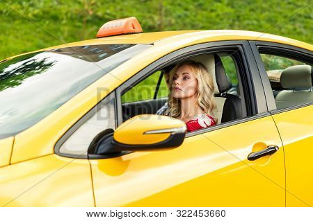 Image Of Female Driver Sitting In Yellow Taxi On Summer Day