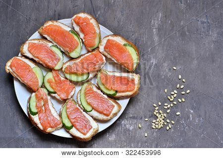 Red Fish Sandwiches With Soft Cheese And Fresh Cucumber On A White Plate On A Shabby Vintage Backgro