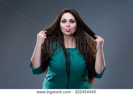 Happy Plus Size Fashion Model In Green Dress, Fat Woman Shows Tongue On Gray Background, Body Positi