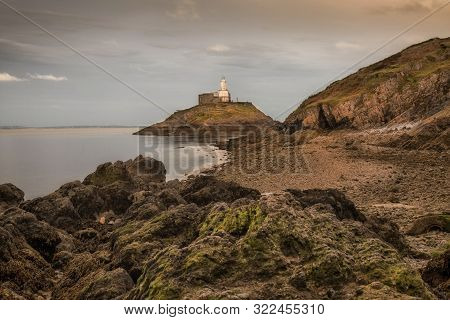 Low Tide Exposing The Rocks Around Mumbles Lighthouse On The Gower Peninsula In Swansea, South Wales
