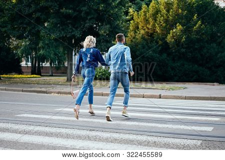 Back View Of Young Happy Couple Running Crosswalk In The Street. Fun, Walking, Dating Concept