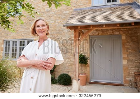 Portrait Of Mature Woman Standing Outside Front Door Of Home