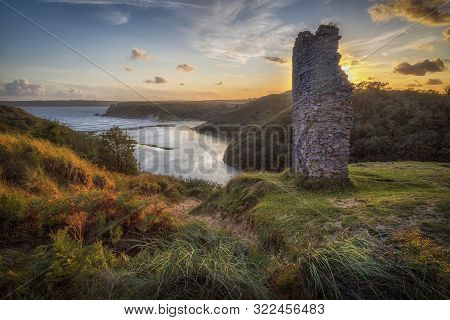 Evening And High Tide At The Remains Of Pennard Castle On The Gower Peninsula, Overlooking Three Cli